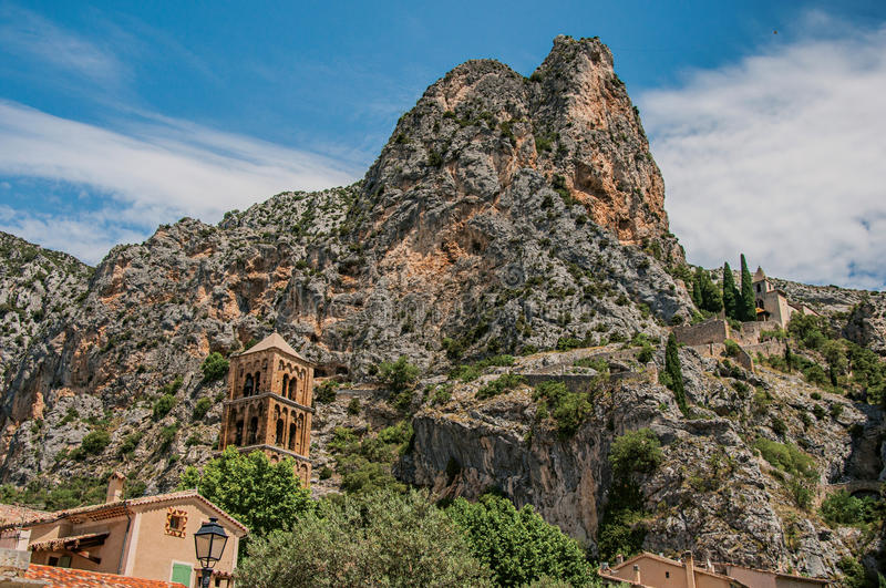 View of the church Notre-Dame de Beauvoir amid the cliffs and steeple of Moustiers-Sainte-Marie. royalty free stock photos