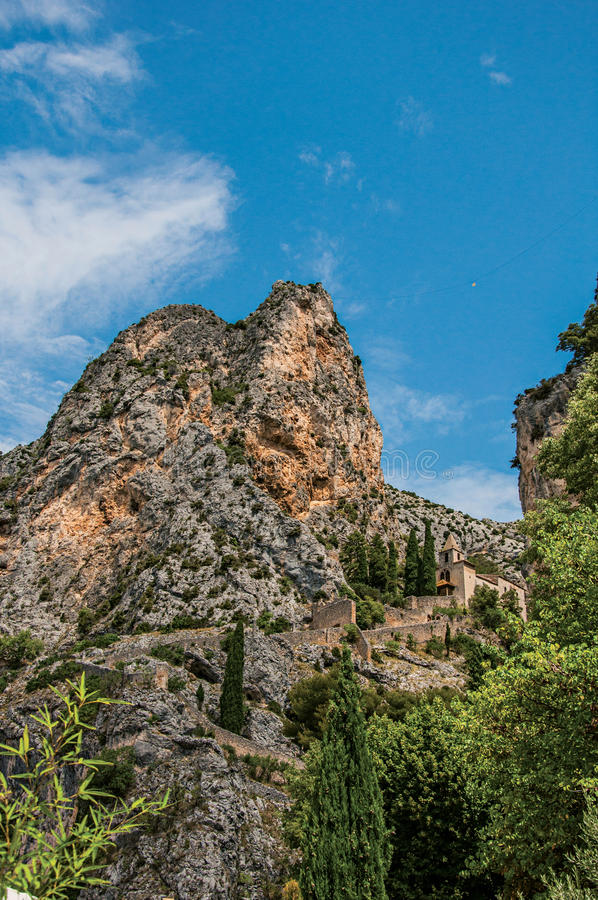 View of the church Notre-Dame de Beauvoir amid the cliffs and steeple of Moustiers-Sainte-Marie. royalty free stock images