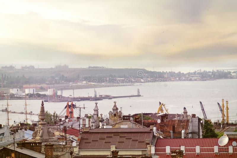 View of the city from above and into the distance the bay of the Black Sea in the evening light. Ukraine. Odessa. Coast of the Bla. Ck Sea. View of the old roofs royalty free stock photo