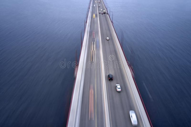 View at city bridge with traffic through river. Amazing bridge through Dnieper river with a traffic blurred in motion in city of Dnipro in Ukraine. It has red royalty free stock photography