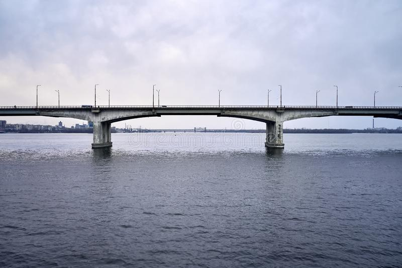 View at city bridge with traffic through river. Cloudy cityscape of Dnipro with bridges through Dnieper river on the sky background in Ukraine. There are moving stock photos