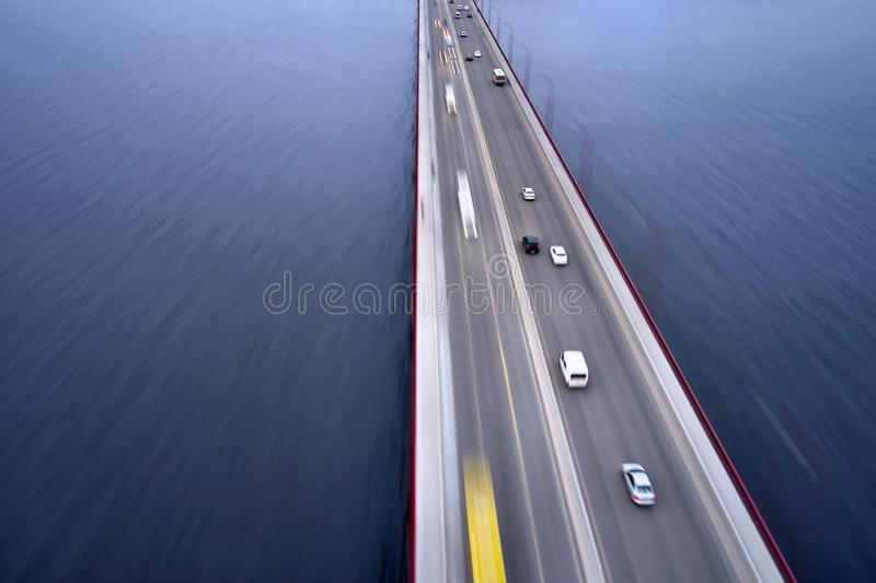 View at city bridge with traffic through river. Wonderful bridge through Dnieper river with a traffic blurred in motion in city of Dnipro in Ukraine. It has red royalty free stock photos