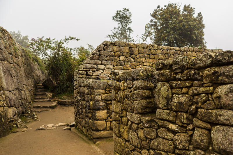 View of the city built in the lost Inca city. Of Machu Picchu, Peru, in foggy and rainy weather royalty free stock image