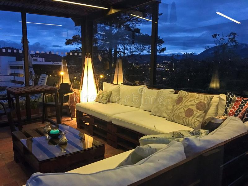 Outdoor Rooftop Patio at Night. View of the city of Cuenca, Ecuador at night from the rooftop deck of a home. Enclosed glass patio with comfy lounge seating and stock images