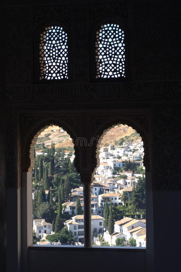 View of the city of Granada in Spain from the palace window. View of the city from the old Moorish castle. The medieval Arab castle. Arched and openwork windows royalty free stock image
