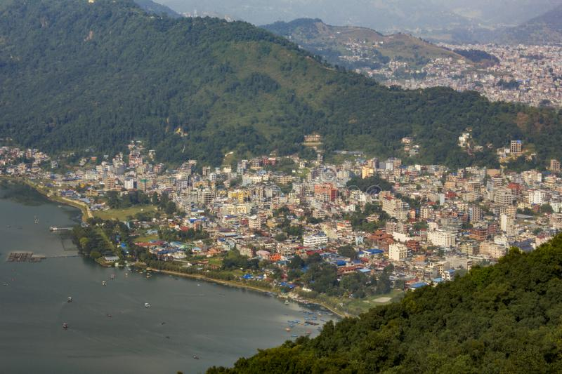 View of the city of Pokhara near the lake Phewa with boats on the water, against the background of the city of the green mountain stock images