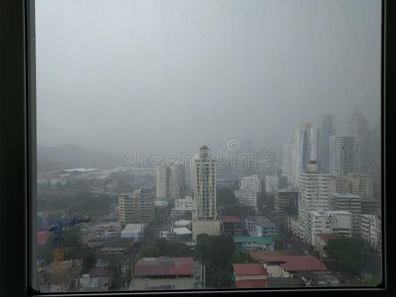 View on the city in the rain. View from a high-rise building onto the urban skyline in the rain