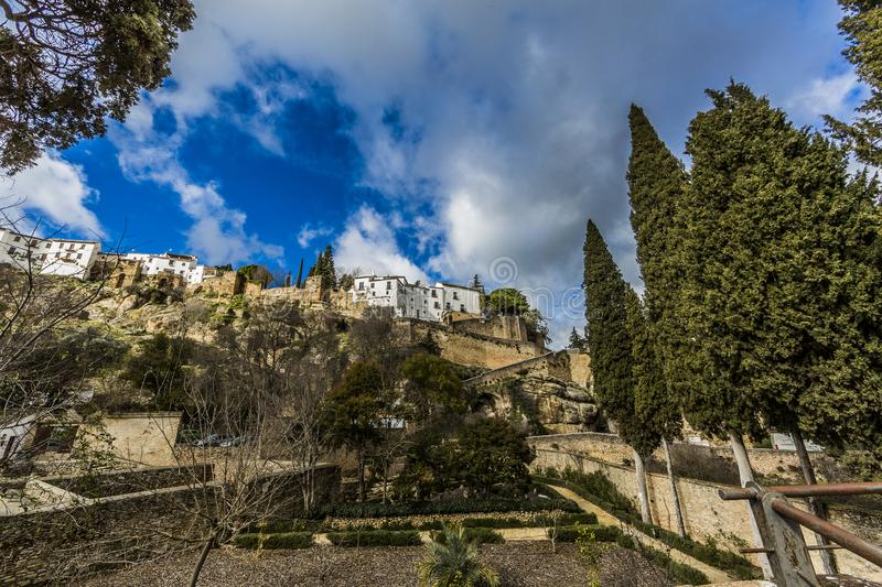 View of the city of Ronda with its white buildings at the top from a lower perspective. Sunny day with abundant clouds in the province of Malaga Spain royalty free stock image