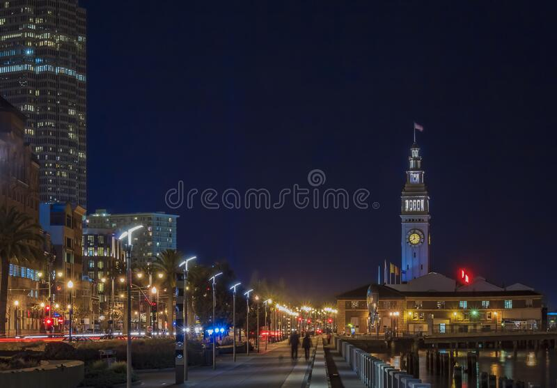 View of the city skyline in the Financial District along the waterfront and Ferry Building at night, San Francisco, USA. San Francisco, USA - February 09 2012 stock image