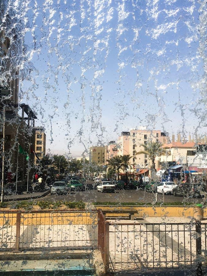 View of the city street through the falling water of the fountain. Jordan, Aqaba. Tourism stock photo