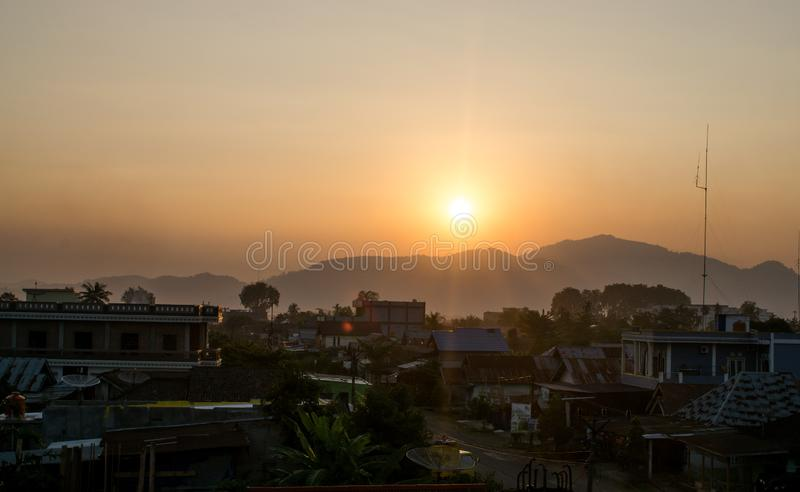 View of the city when the sun sets. Dus, dusk, mountain, landscape, trees, house, sunlight, bright, shine, sunshine, sky, yellow, gold, street royalty free stock photography