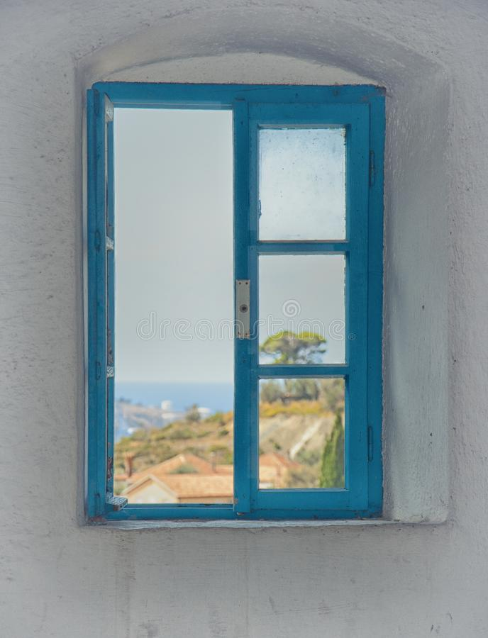 View of the city from the window of the building in the fortress of the old bar, Montenegro. Blue old window among white walls. royalty free stock photo