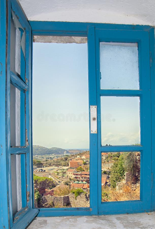 View of the city from the window of the building in the fortress of the old bar, Montenegro. Blue old window among white walls. Summer royalty free stock photography