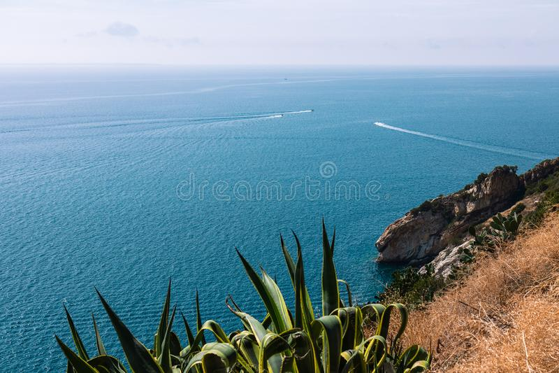 The view from the cliff to the calm blue sea of Elba Island crossed by high-speed boats. royalty free stock photography