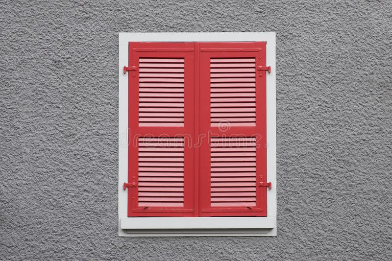 Closed red wooden window shutters against grey wall royalty free stock image