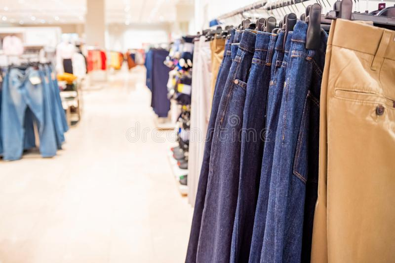 Trousers hang on rails in modern clothes shop. View of clothes shop interior with various pants on hanging rail royalty free stock photos
