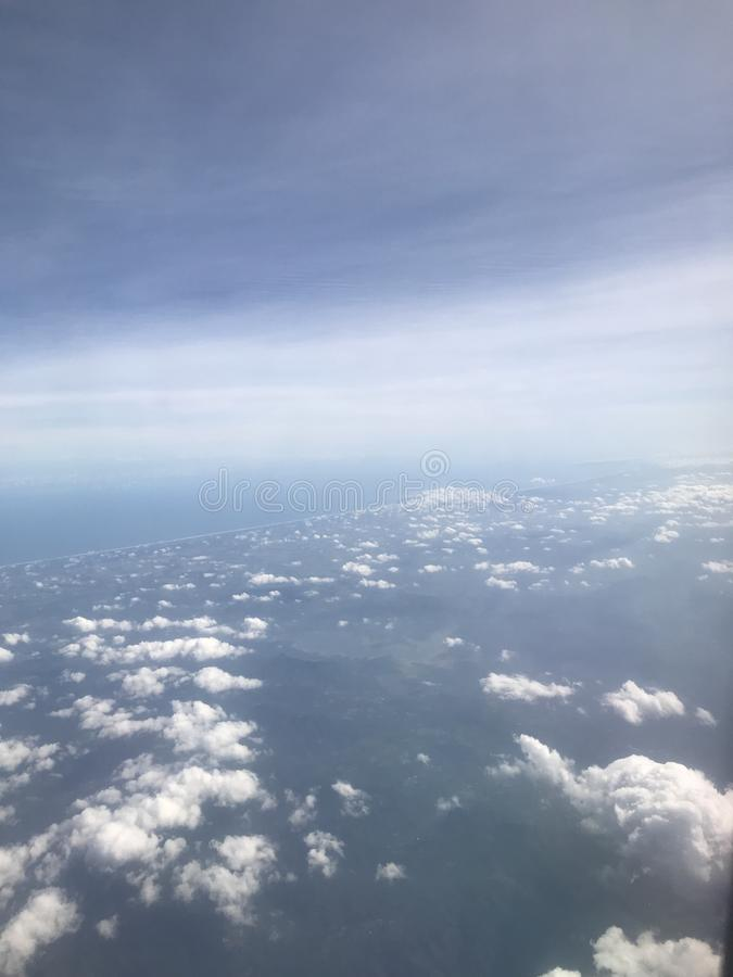 View of clouds from the plane. all look bright blue stock photography