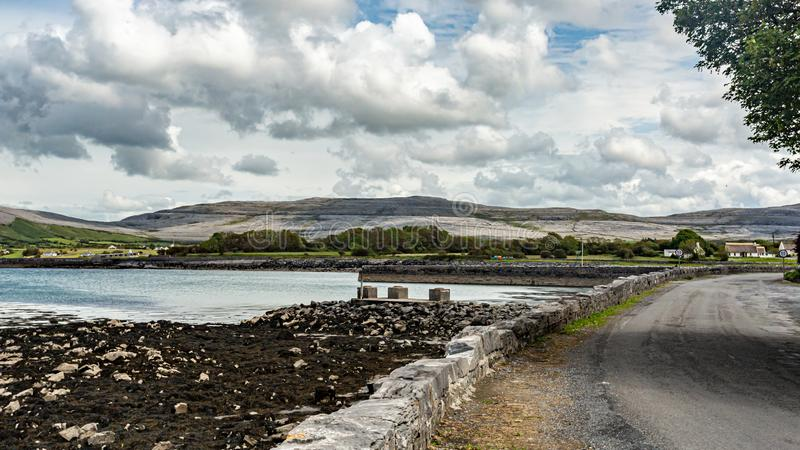 View of the coastal area of ​​Ballyvaughan, R477 road. Geosite and geopark, Wild Atlantic Way, cloudy spring day in County Clare, west coast of stock image