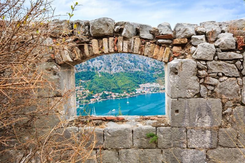 Window in old stone wall of medieval fortress. View of coastal town at foot of mountains and sea bay from window in old stone wall of medieval fortress in royalty free stock image