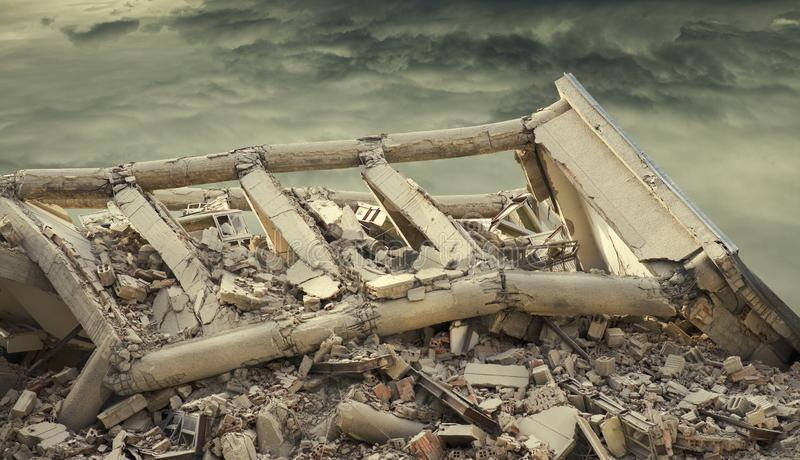 View on a collapsed concrete industrial building with dark dramatic sky above. Damaged house. royalty free stock photo