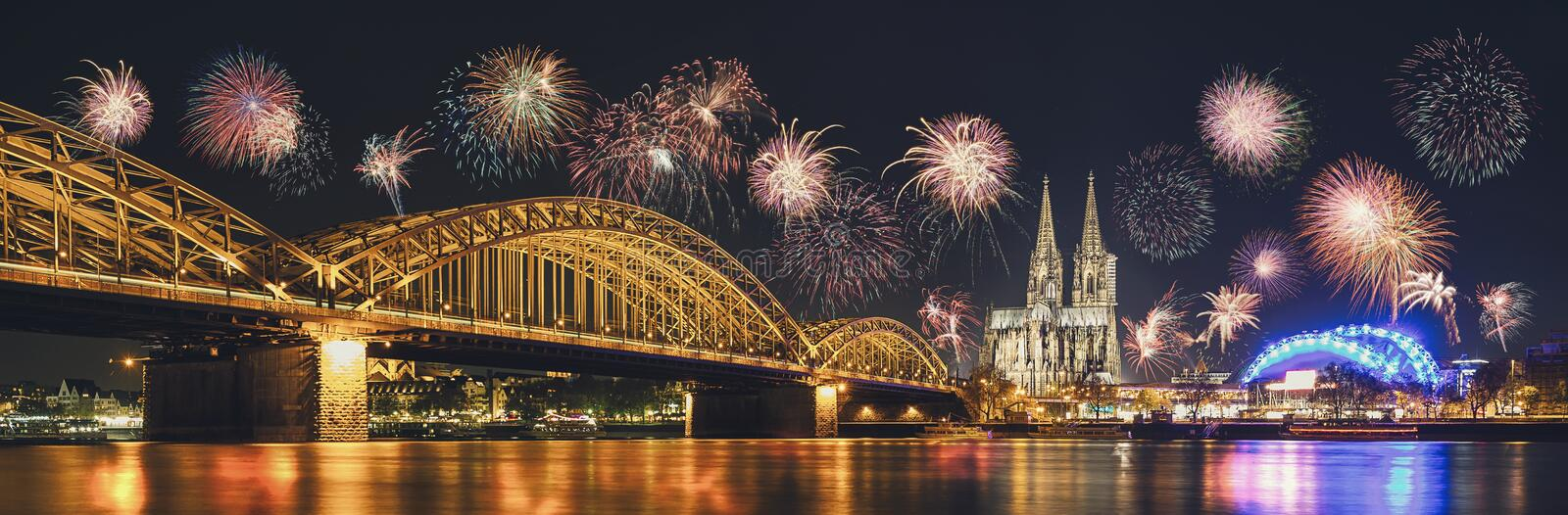 Cologne Cathedral and Hohenzollern Bridge with Fireworks on New. View of Cologne city at new years eve with amazing fireworks over the Cologne Cathedral and royalty free stock image