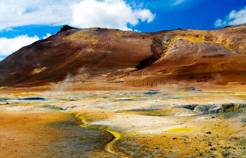 View on colorful valley with yellow sulfur deposits in volcanic barren dry landscape with red mountains background royalty free stock photos