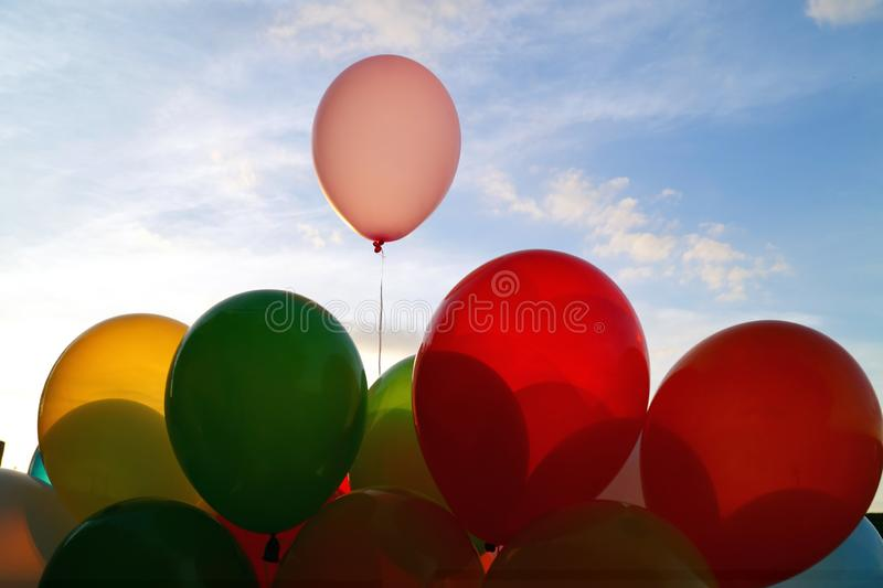 Mix of colorful balloons over blue sky background and sun shining through clouds, stock images