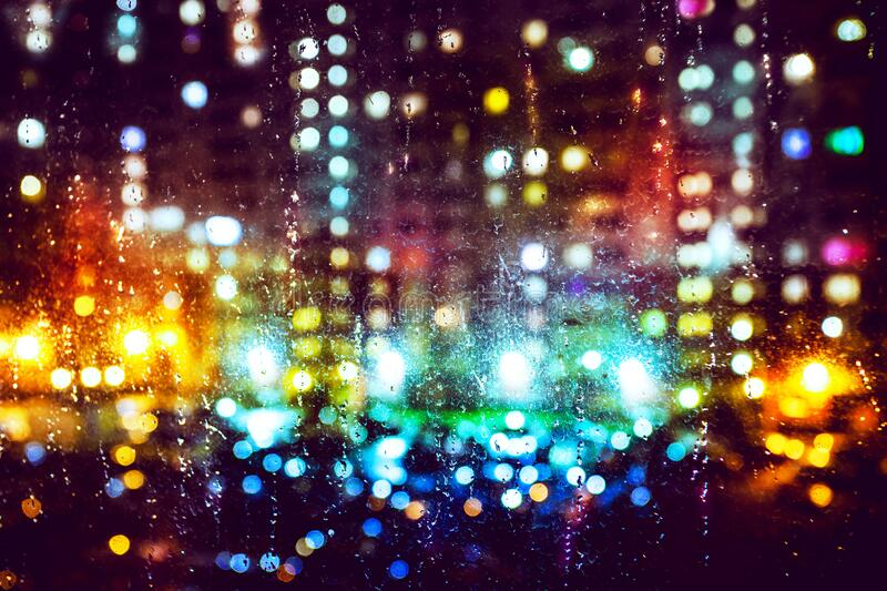 A view of colourful blurred lights through the wet night window stock images