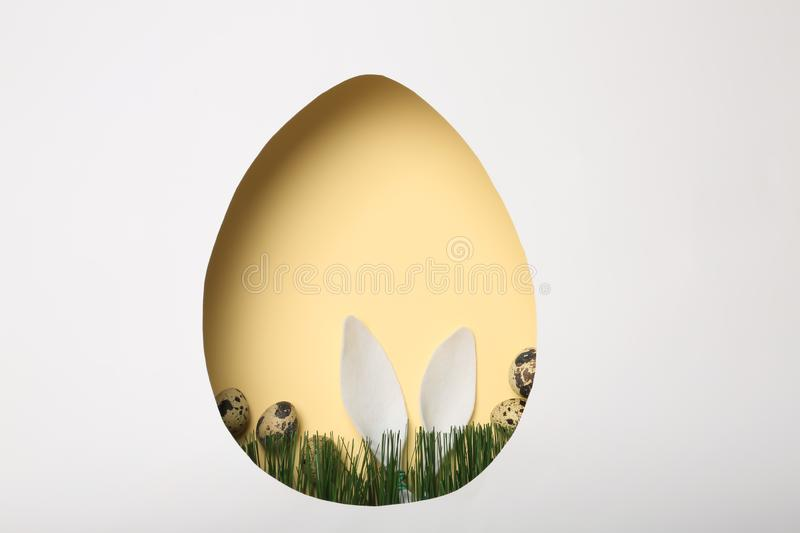 View of composition with Easter bunny ears on color background through egg shaped hole, top view. Space for text royalty free stock images