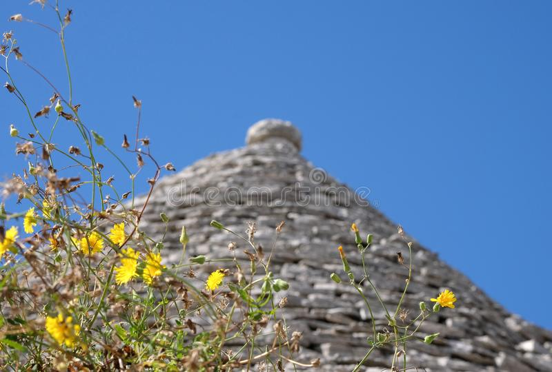 View of the conical dry stone roof of a traditional trullo house in Alberobello in Puglia Italy stock images