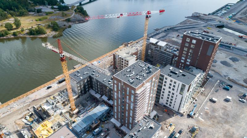 View of a construction crane from above looking down onto a metropolitan city scape during daytime.  royalty free stock photos