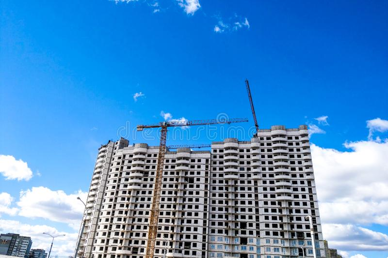 View of the construction cranes and the new house under construction against the blue sky. stock images
