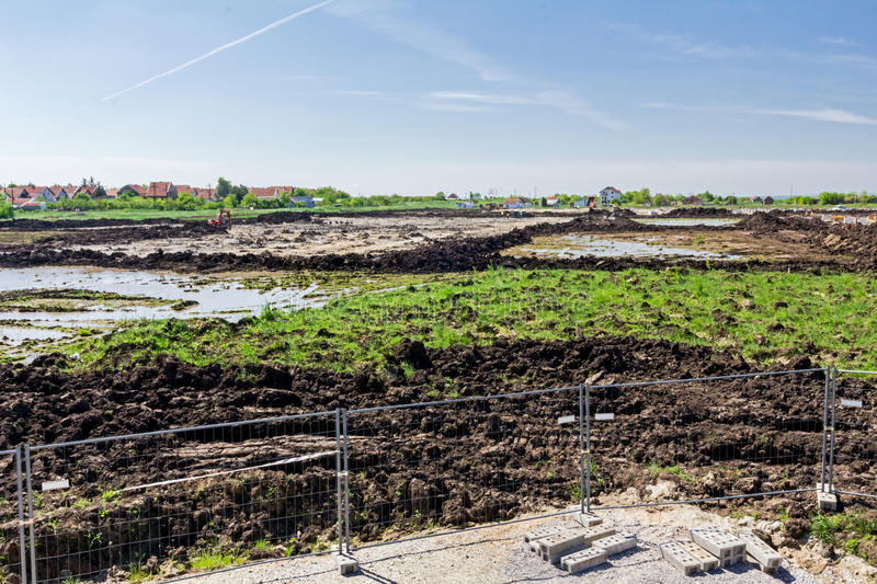 View on the construction site above the fence wire. Landscape transform into urban area with machinery, people are working. View on construction site royalty free stock images
