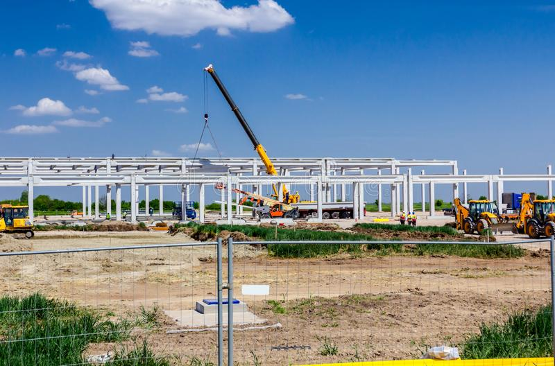 View on the construction site over fence wire. Landscape transform into urban area with machinery, people are working on unfinished modern edifice. View on royalty free stock photo