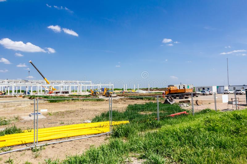 View on the construction site over fence wire. Landscape transform into urban area with machinery, people are working on unfinished modern edifice. View on stock photo