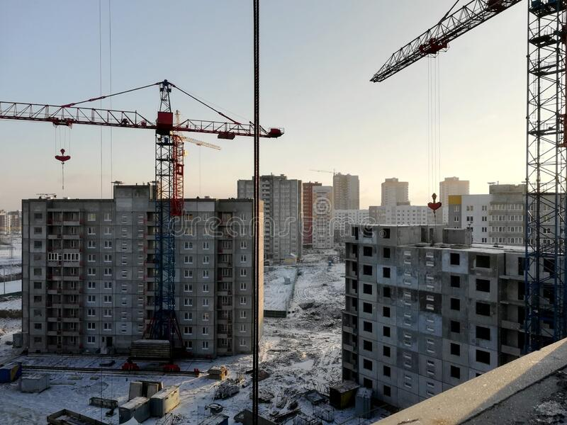 View of a construction site on a winter sunny frosty day. The construction of residential buildings using tower cranes.  royalty free stock photography