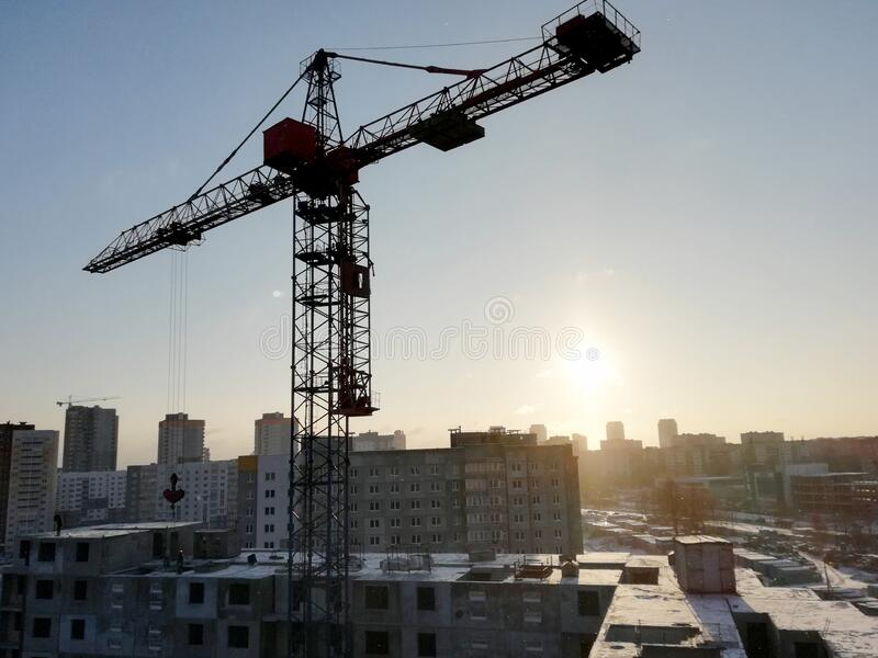 View of a construction site on a winter sunny frosty day. The construction of residential buildings using tower cranes.  stock photography
