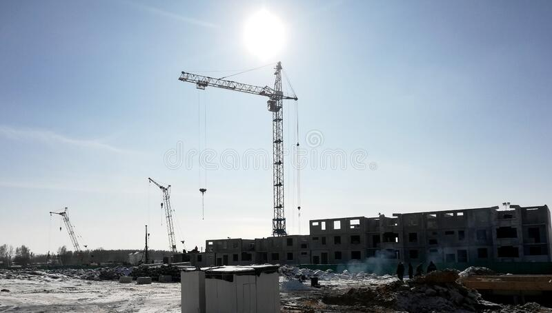 View of a construction site on a winter sunny frosty day. The construction of residential buildings using tower cranes royalty free stock photography