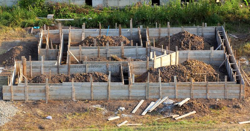 View of construction site and wooden house foundation in preparation process. Cellar construction. Concrete foundation for a new royalty free stock photo