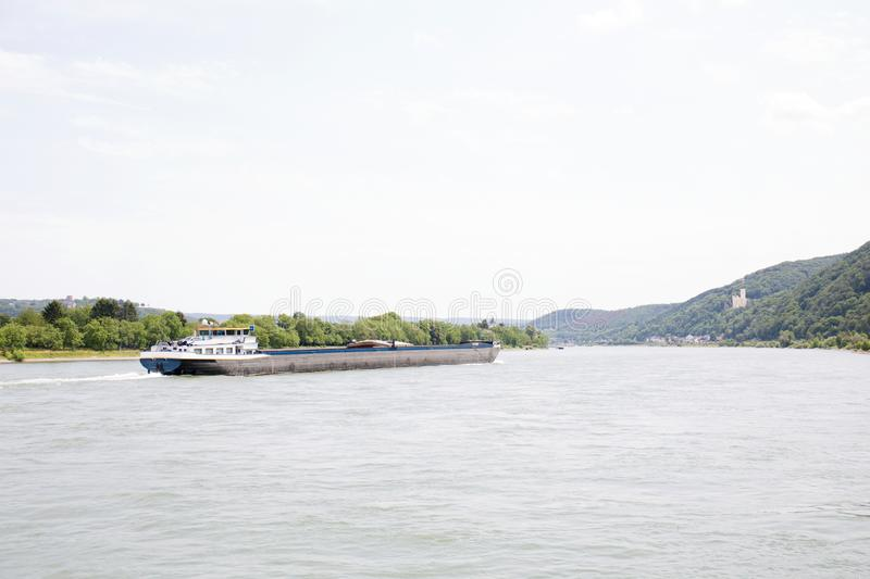 View on a container ship on and the natural landscape at the rhine in Koblenz rhine and surrounding stock photography