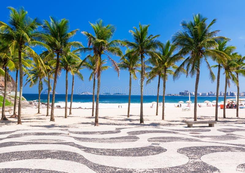 View of Copacabana beach with palms and mosaic of sidewalk in Rio de Janeiro stock photos