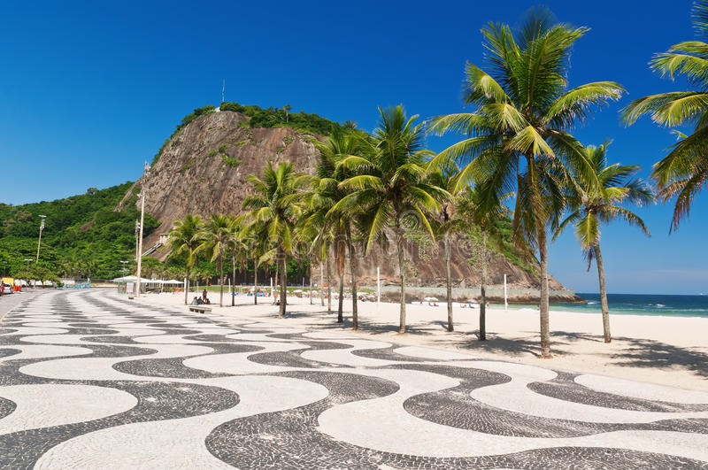 View of Copacabana and Leme beach with palms and mosaic of sidewalk in Rio de Janeiro royalty free stock images