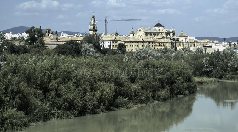 View of Cordoba from the Guadalquivir river. A view of Cordoba from the Guadalquivir river, showing the Torre Companario Bell tower and the Mezquita Cathedral royalty free stock images