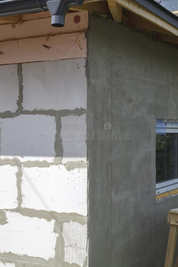 View of corner of house under construction, one wall of which is finished with base plaster layer, and second is not yet. Industrial, plastic, object, block stock images