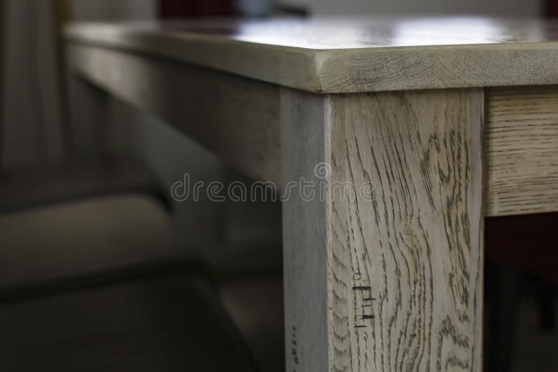 View of the corner of the table with a wooden texture and smooth countertop lit natural light from the window stock photography