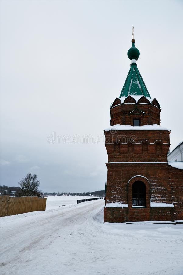 View of the corner tower of the fence Nikolsky monastery and the Volkhov River in winter. stock photos