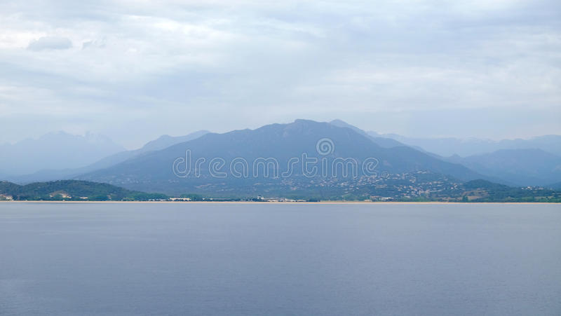 View on the Corsica island in France. View on the sea and the island Corsica in the evening with chain of mountains like backstage, France stock image