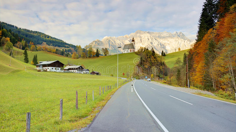 View of a country road passing by a farm land with a church on top of the hill and Mountain Hochkoenig. Lighted up by alpenglow in the background in Dienten royalty free stock photo