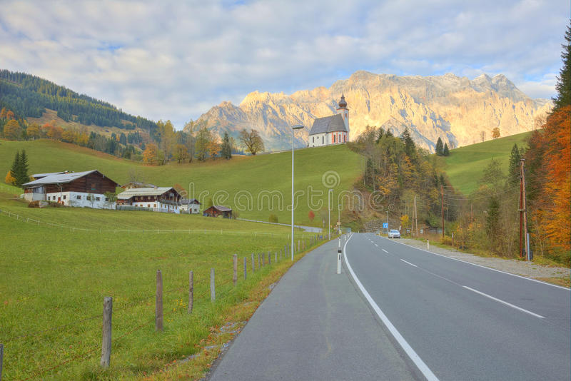 View of a country road passing by a farm land with a church on top of the hill and Mountain Hochkoenig. Lighted up by alpenglow in the background in Dienten royalty free stock images