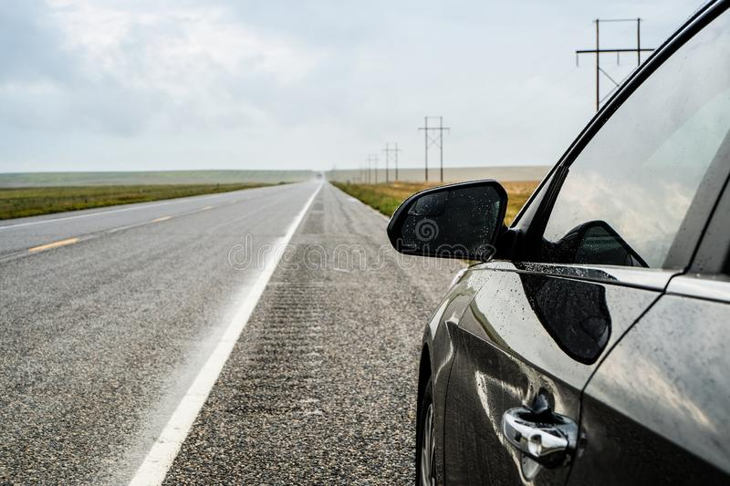 View of countryside asphalt road on a rainy day, black car parked on road side. stock photography
